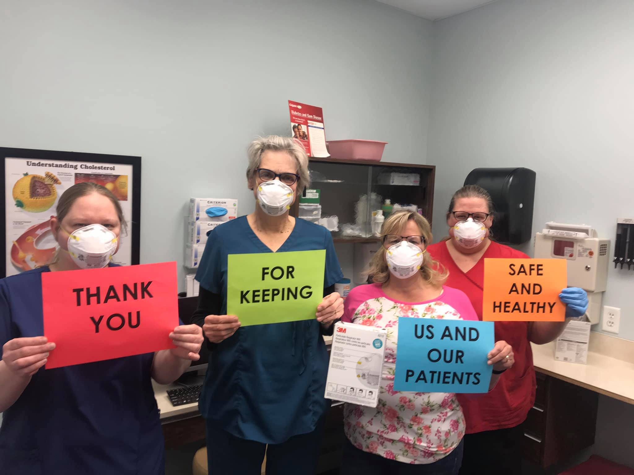 Medical staff holding up signs that say 'Thank you for keeping us and our patients safe and healthy.'
