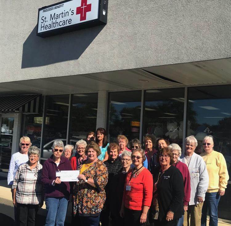 Curiosity Shop staff awarding a check to St. Martin's Healthcare
